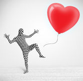 Il tipo sveglio nel vestito del corpo del morpsuit che esamina un pallone ha modellato il cuore Immagine Stock Libera da Diritti