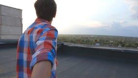 Il tipo tiene la mano del suo ragazzo e funziona per orlare del tetto per ammirare la vista Seguami colpo del giovane per tirare  stock footage