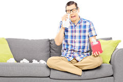Il tipo triste che si siede su un sofà e che pulisce il suo osserva dal gridare Fotografie Stock Libere da Diritti