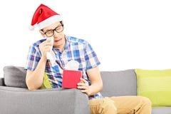 Il tipo triste con il cappello di Santa su un sofà che pulisce il suo osserva dal gridare Fotografie Stock Libere da Diritti