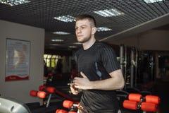 Il tipo, uomo in guantoni da pugile, nella palestra, mette in mostra l'addestramento, Fotografie Stock