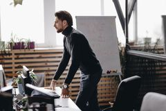 Il tipo vestito in vestiti casuali di stile dell'ufficio sta allo scrittorio nell'ufficio moderno fornito di mobili d'ufficio mod immagini stock