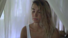 Il tipo video del ritratto di bello modello, donna ritiene a pace con tutto il mondo, meditazione nell'area della camera da letto video d archivio
