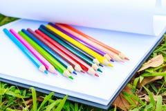 Il tiraggio aperto ed il pastello del Libro Bianco della mano sono sulla carta Il Libro Bianco è sull'erba fotografia stock
