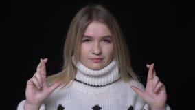 Il tiro del primo piano di giovane femmina caucasica graziosa in maglione che gesturing le dita crosssed essere sguardo prometten stock footage