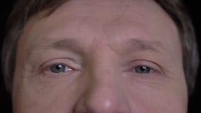 Il tiro del primo piano del mezzo ha invecchiato il fronte maschio caucasico con gli occhi grigi che esaminano diritto la macchin stock footage