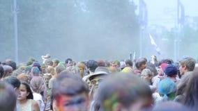 Il tiro della gente colora l'un l'altro durante la celebrazione di Holi a Mosca stock footage
