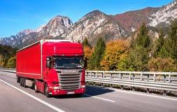 Il TIROLO, AUSTRIA - 14 ottobre 2017: Camion rosso su una strada ad alta velocità della montagna Fotografie Stock Libere da Diritti