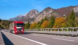 Il TIROLO, AUSTRIA - 14 ottobre 2017: Camion rosso su una strada ad alta velocità della montagna Fotografia Stock Libera da Diritti