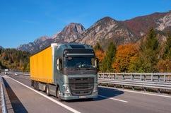 Il TIROLO, AUSTRIA - 14 ottobre 2017: Un camion con un furgone giallo su una strada ad alta velocità della montagna Fotografia Stock