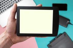 Il tocco della mano sullo schermo vuoto della compressa sopra la vista variopinta del piano d'appoggio, lascia lo spazio per espo immagine stock libera da diritti