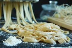 Il tolyatelli casalingo esce dalla macchina per pasta, spruzzata con farina Immagine Stock