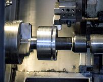 Il tornio di CNC estrae la parte della puleggia del pezzo in lavorazione del metallo, tornio moderno per metallo che elabora, il  immagine stock