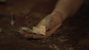 Il tossicomane incosciente, passa in pieno delle pillole e della polvere della cocaina che cade sulla tavola stock footage