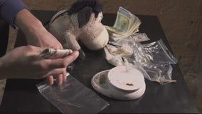 Il trafficante di droga imballa le droghe - eroina, cocaina - in pacchetti e li pesa Prende le droghe dal nascondiglio e video d archivio