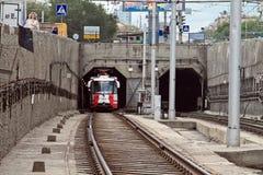 Il tram ad alta velocità parte dal tunnel del sottopassaggio. Fotografie Stock