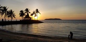 Il tramonto caldo, la spiaggia, la madre e la figlia giocano l'acqua, l'ombra, mare dorato fotografie stock