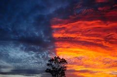 Il tramonto drammatico ed il cielo rosso e blu di colore fotografia stock