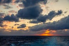 Il tramonto e l'insieme drammatico delle nuvole che vanno alla deriva sopra le acque tropicali del mar dei Caraibi sono accesi en Fotografie Stock