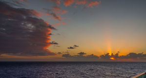 Il tramonto e l'insieme drammatico delle nuvole che vanno alla deriva sopra le acque tropicali del mar dei Caraibi sono accesi en Fotografia Stock Libera da Diritti