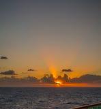Il tramonto e l'insieme drammatico delle nuvole che vanno alla deriva sopra le acque tropicali del mar dei Caraibi sono accesi en Immagine Stock