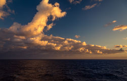 Il tramonto e l'insieme drammatico delle nuvole che vanno alla deriva sopra le acque tropicali del mar dei Caraibi sono accesi en Immagini Stock Libere da Diritti