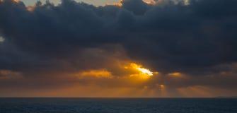 Il tramonto e l'insieme drammatico delle nuvole che vanno alla deriva sopra le acque tropicali del mar dei Caraibi sono accesi en Immagini Stock