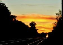 Il tramonto emette luce sulle rotaie di un binario ferroviario nella periferia di Chicago come approcci del treno, splendere dei  Fotografie Stock