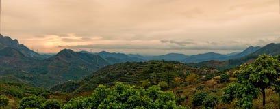 Il tramonto ha illuminato in su il cielo e le montagne Fotografie Stock