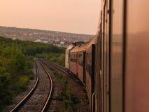 Il tramonto, il treno ed il viaggio fanno un bello giorno Immagini Stock Libere da Diritti