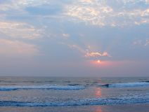 Il tramonto, le nuvole e la riflessione in mare Payyambalam acqua tirano, Kannur, Kerala, India fotografie stock libere da diritti