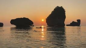 Il tramonto romantico alle pietre della roccia del calcare della costa dell'Oceano Indiano aumenta sopra la gente in kajak, ondul stock footage