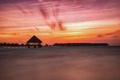 Il tramonto romantico e variopinto sopra l'acqua alloggia in Maldive Fotografia Stock