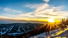 Il tramonto sopra gli alberi innevati nel paesaggio dell'inverno di alto alpino alla stazione sciistica del Sun alza Immagine Stock