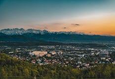 Il tramonto sopra la città di Almaty e una vista del Kok Tobe TV si elevano Fotografia Stock