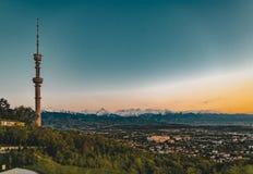 Il tramonto sopra la città di Almaty e una vista del Kok Tobe TV si elevano Immagini Stock Libere da Diritti