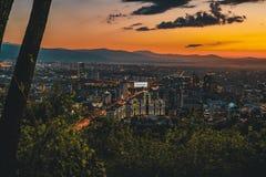 Il tramonto sopra la città di Almaty e una vista del Kok Tobe TV si elevano Immagini Stock