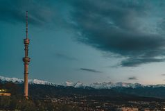 Il tramonto sopra la città di Almaty e una vista del Kok Tobe TV si elevano Immagine Stock
