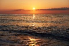 Il tramonto variopinto sopra il mare dallo scontrarsi ondeggia Composizione nella natura fotografia stock