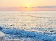 Il tramonto variopinto sopra il mare dallo scontrarsi ondeggia Composizione nella natura immagine stock