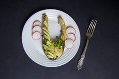 Il trancio di pesce con l'avocado ed il ravanello fresco è servito su un piatto bianco Immagine Stock