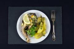 Il trancio di pesce con il limone e le patate fritte è servito su un piatto bianco Immagini Stock Libere da Diritti
