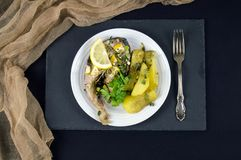 Il trancio di pesce con il limone e le patate fritte è servito su un piatto bianco Fotografia Stock Libera da Diritti