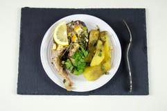 Il trancio di pesce con il limone e le patate fritte è servito su un piatto bianco Fotografia Stock