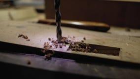 Il trapano del metallo fa un foro in dettaglio di legno trapano retroilluminato Primo piano 4K stock footage