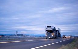 Il trasportatore classico dell'automobile del camion dei semi alla moda in colonna sulla strada di notte è Fotografie Stock Libere da Diritti