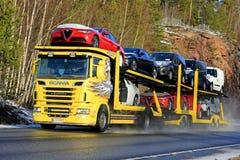 Il trasportatore di automobile giallo di Scania R500 trasporta i nuovi veicoli Fotografie Stock Libere da Diritti