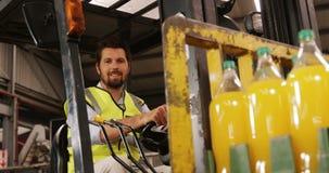 Il trasporto maschio del lavoratore imbottiglia il carrello elevatore nell'industria di bottiglia archivi video