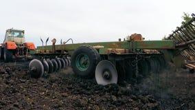 Il trattore abbassa il mulino dell'aratro in terra per il terreno arabile del campo video d archivio
