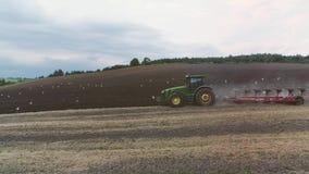 Il trattore agricolo ara un grande campo archivi video